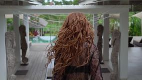 Mujer atractiva joven del rojo-pelo en ropa interior negra que camina y que circunda en el chalet a cámara lenta metrajes