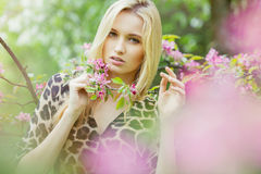 Mujer atractiva joven en árboles florecientes de la primavera Fotografía de archivo libre de regalías