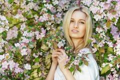 Mujer atractiva joven en árboles florecientes de la primavera Imágenes de archivo libres de regalías