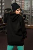 Mujer atractiva joven en chaqueta negra con la capilla Fotos de archivo libres de regalías