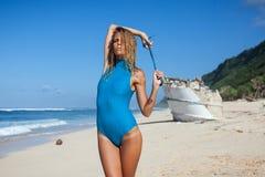 Mujer atractiva joven en el traje de baño que presenta en la playa arenosa durante d3ia Fotos de archivo libres de regalías