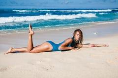 Mujer atractiva joven en el traje de baño que presenta en la playa arenosa durante d3ia Fotografía de archivo