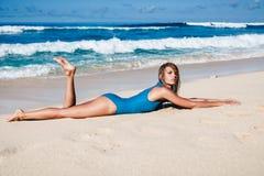 Mujer atractiva joven en el traje de baño que presenta en la playa arenosa durante d3ia Fotografía de archivo libre de regalías