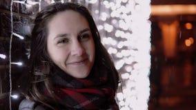 Mujer atractiva joven en la nieve que cae en la noche de la Navidad que mira la cámara que coloca la pared cercana de las luces, Imagen de archivo libre de regalías