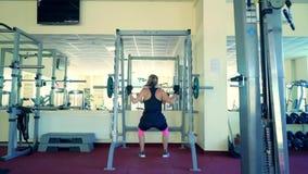 Mujer atractiva joven en los guantes protectores que trabajan difícilmente haciendo posiciones en cuclillas cargadas en el gimnas metrajes