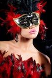 Mujer atractiva joven en media máscara del partido negro Imagenes de archivo