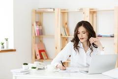 Mujer atractiva joven en un escritorio de oficina moderno, trabajando con el ordenador portátil y pensando en algo Imagen de archivo libre de regalías