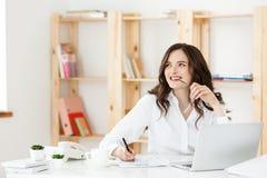 Mujer atractiva joven en un escritorio de oficina moderno, trabajando con el ordenador portátil y pensando en algo Fotografía de archivo
