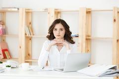 Mujer atractiva joven en un escritorio de oficina moderno, trabajando con el ordenador portátil y pensando en algo Imagenes de archivo