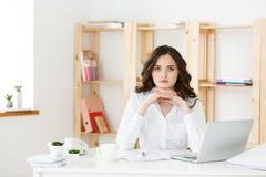 Mujer atractiva joven en un escritorio de oficina moderno, trabajando con el ordenador portátil y pensando en algo Fotos de archivo