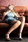 Mujer atractiva joven en un sofá de lujo Imagen de archivo libre de regalías