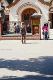Mujer atractiva joven en un vestido del estampado leopardo al lado de la galería de Tretyakov del estado llamada por teléfono Fotos de archivo libres de regalías
