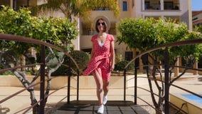 Mujer atractiva joven en vestido rojo con las gafas de sol y el sombrero que camina en el puente sobre la piscina en el hotel GA  almacen de video