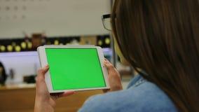 Mujer atractiva joven en vidrios que mira el vídeo en la tableta con la pantalla verde en el café Primer Llave de la croma almacen de metraje de vídeo