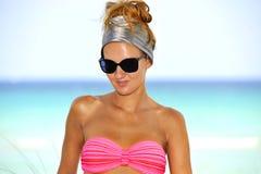Mujer atractiva joven feliz en el bikini rosado que presenta en la playa del paraíso Fotos de archivo libres de regalías