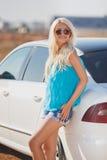 Mujer atractiva joven hermosa cerca de un coche al aire libre Foto de archivo libre de regalías