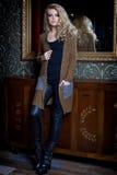 Mujer atractiva joven hermosa con el pelo rubio largo, maquillaje brillante Smokey Eyes que lleva un suéter al lado de un aparado Imágenes de archivo libres de regalías