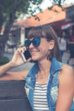 Mujer atractiva joven hermosa que usa el smartphone que se sienta en un banco en el parque Isla de Bali, Indonesia Imagen de archivo