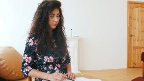 Mujer atractiva joven inspiredly que dibuja en el papel almacen de video