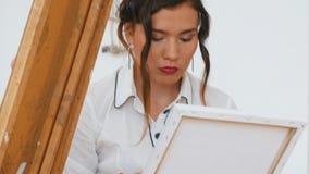 Mujer atractiva joven inspiredly que dibuja en lona metrajes