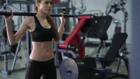 mujer atractiva joven 4K que trabaja difícilmente en el gimnasio que hace posiciones en cuclillas cargadas almacen de metraje de vídeo