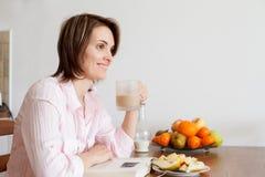Mujer atractiva joven, leyendo un libro en casa, comiendo frutas Imágenes de archivo libres de regalías