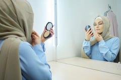 Mujer atractiva joven musulmán en hijab beige y el vestido azul tradicional que hacen maquillaje foto de archivo