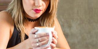 Mujer atractiva joven que bebe una bebida caliente deliciosa Imagen de archivo libre de regalías