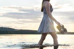 Mujer atractiva joven que camina en agua del lago en la puesta del sol imagen de archivo libre de regalías