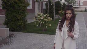 Mujer atractiva joven que camina en la calle que mira la cámara metrajes