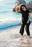 Mujer atractiva joven que camina en una playa soleada en la orilla Viajero y blogger fotografía de archivo