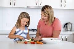 Mujer atractiva joven que cocina así como sus pequeños 6 o 7 años rubios hermosos dulces del sa preparado feliz sonriente de la h Fotos de archivo