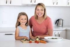 Mujer atractiva joven que cocina así como sus pequeños 6 o 7 años rubios hermosos dulces del sa preparado feliz sonriente de la h Fotografía de archivo libre de regalías
