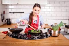 Mujer atractiva joven que cocina en cocina Fotos de archivo