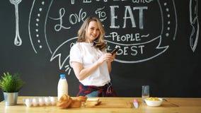 Mujer atractiva joven que cocina los huevos revueltos en cocina por mañana, sonriendo, ama de casa positiva feliz, sana almacen de video