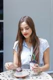 Mujer atractiva joven que come la torta con café en café al aire libre Imagen de archivo libre de regalías