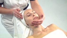 Mujer atractiva joven que consigue el tratamiento del balneario sobre el fondo blanco metrajes