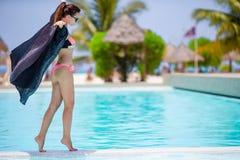 Mujer atractiva joven que disfruta de resto al borde de piscina al aire libre Imágenes de archivo libres de regalías