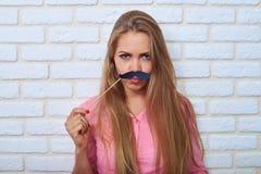 Mujer atractiva joven que frunce el ceño divertida que sostiene el bigote de papel ov Imagenes de archivo