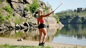 Mujer atractiva joven que hace el selfie cerca del río almacen de video