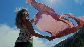 Mujer atractiva joven que hace girar alrededor con la bufanda almacen de video