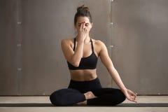 Mujer atractiva joven que hace la respiración alterna de la ventana de la nariz, gris Foto de archivo libre de regalías