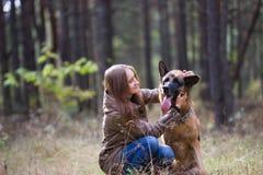 Mujer atractiva joven que juega con el perro de pastor alemán al aire libre en el parque del otoño, cierre para arriba Fotografía de archivo libre de regalías