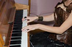 Mujer atractiva joven que juega el piano Imagenes de archivo