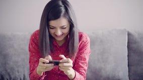 Mujer atractiva joven que juega en smartphone en casa almacen de metraje de vídeo