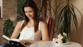 Mujer atractiva joven que lee el libro interesante mientras que se sienta en silla cómoda en la sala de estar almacen de metraje de vídeo