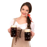 Mujer atractiva joven que lleva un dirndl con el aislante de dos tazas de cerveza foto de archivo