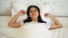 Mujer atractiva joven que miente en la cama, disfrutando de la mañana en casa Muchacha que mira la cámara y la sonrisa almacen de metraje de vídeo