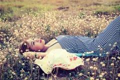 Mujer atractiva joven que miente en la hierba que acerca a su mirada del sombrero en SK Fotografía de archivo