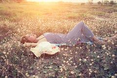 Mujer atractiva joven que miente en la hierba que acerca a su sombrero Fotografía de archivo libre de regalías